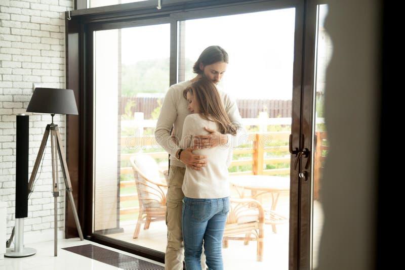 Jeune homme et femme étreignant la position à la maison, reconcilia de couples photos stock