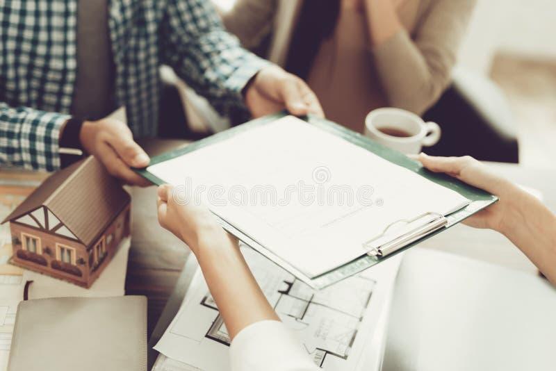 Jeune homme et femme avec l'agent immobilier de sourire dans le bureau photo stock