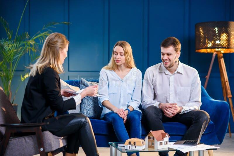 Jeune homme et femme caucasiens sur la réunion avec l'agent immobilier, dessinateur d'intérieurs, décorateur photos libres de droits