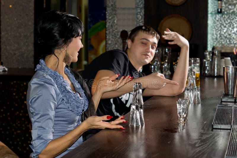 Jeune homme et femme contestant la dernière boisson image stock