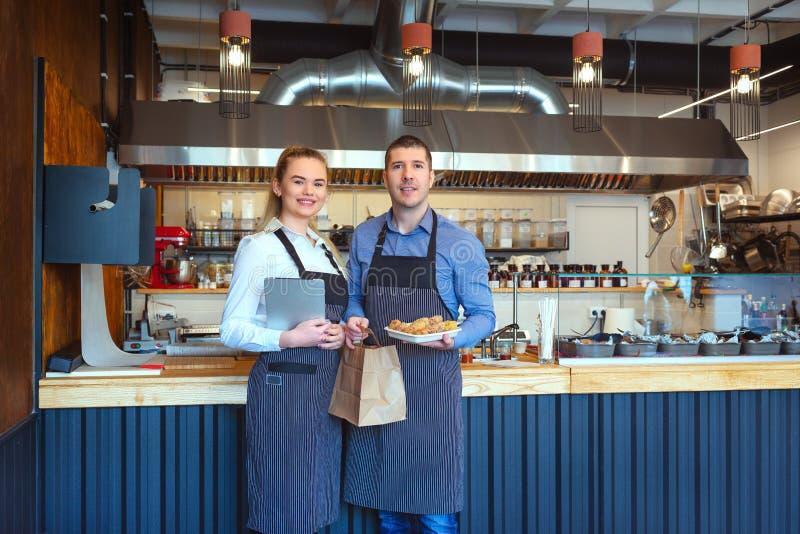 Jeune homme et femme de sourire à l'aide du comprimé au petit restaurant de restaurant photo libre de droits