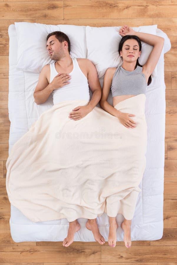 Jeune homme et femme dormant ensemble dans le lit photographie stock