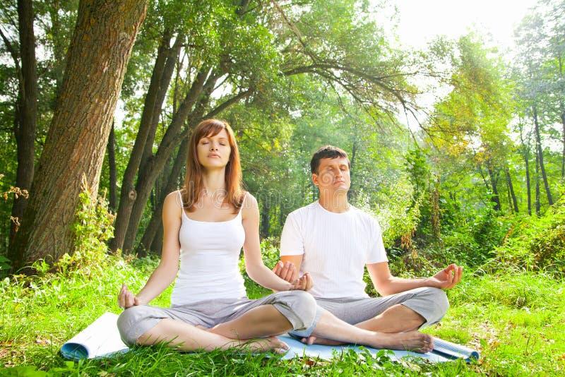 Jeune homme et femme faisant le yoga dans le jardin photo stock