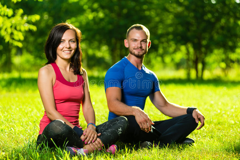 Jeune homme et femme faisant le yoga en parc ensoleillé d'été images stock