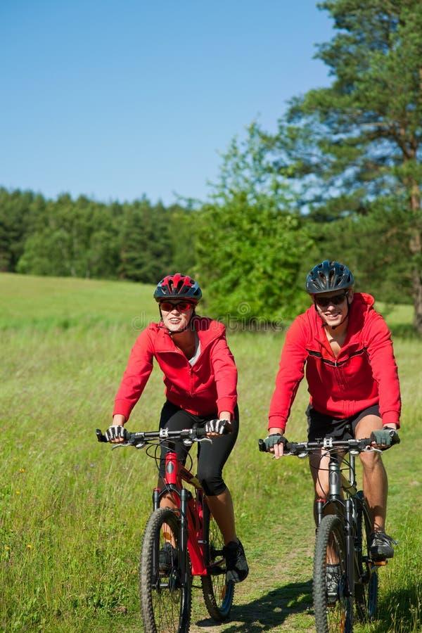 Jeune homme et femme faisant un cycle dans la nature photos libres de droits