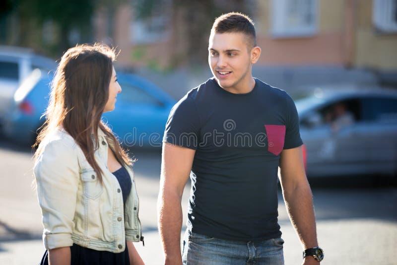 Jeune homme et femme marchant sur la rue photographie stock libre de droits