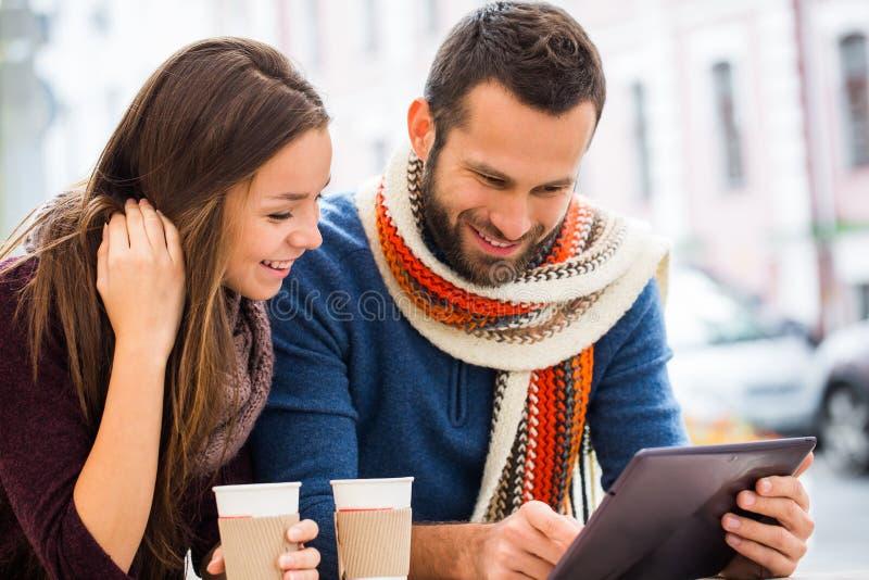 Jeune homme et femme parlant, ils ont l'amusement, ils ont dans leurs mains le comprimé Ils boivent du café ou du thé photos stock