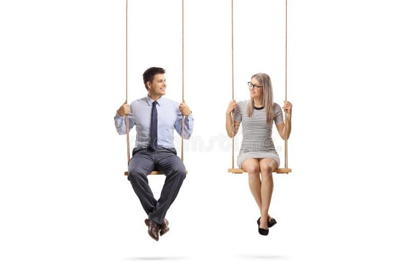 Jeune homme et femme s'asseyant sur une oscillation et regardant l'un l'autre images libres de droits