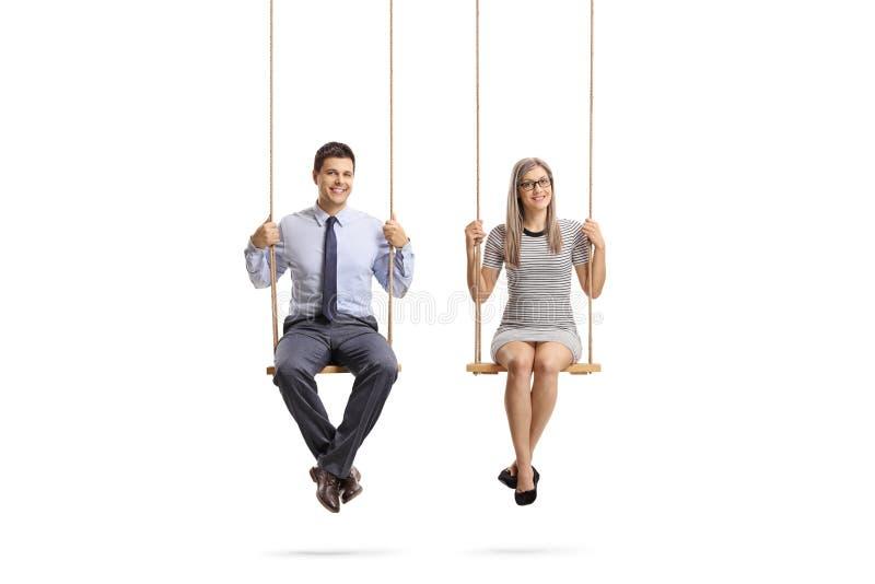 Jeune homme et femme s'asseyant sur une oscillation et souriant à la caméra image libre de droits