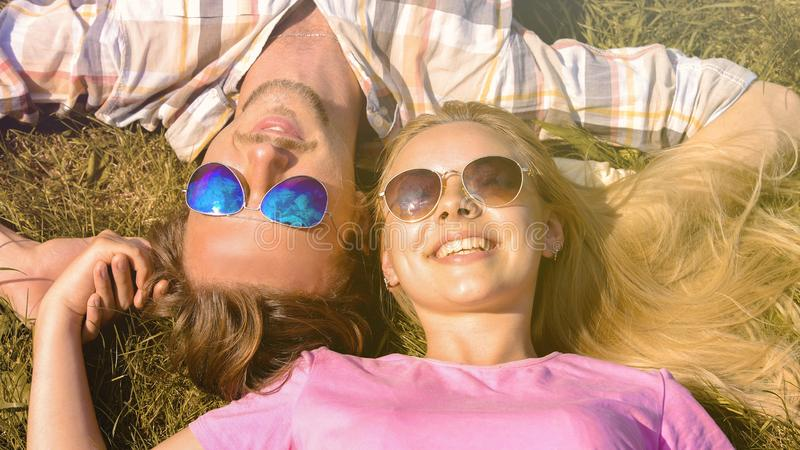 Jeune homme et femme se trouvant sur l'herbe, souriant, tenant des mains, appréciant des vacances photos stock