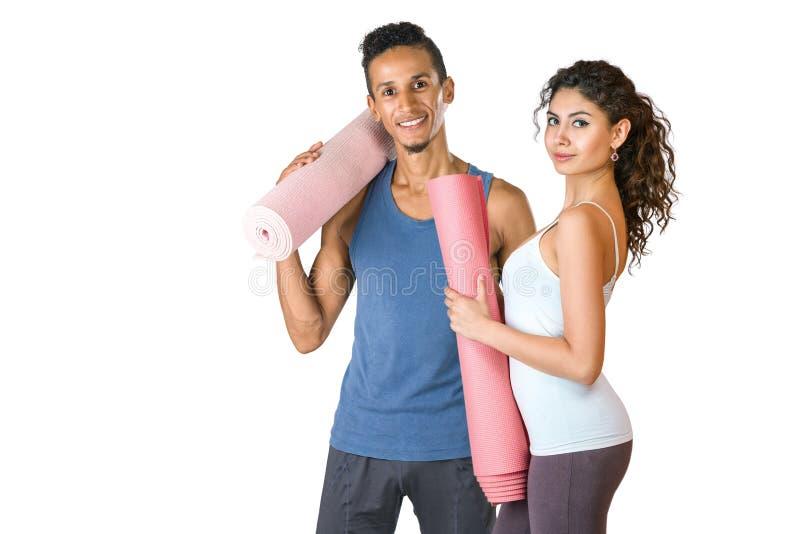 Jeune homme et femme tenant le tapis de yoga images stock