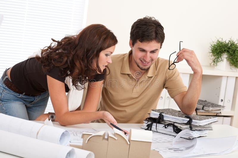 Jeune homme et femme travaillant au bureau d'architecte photo stock