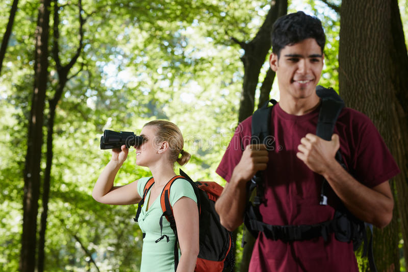Jeune homme et femme trimardant avec des jumelles photographie stock libre de droits