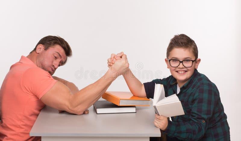 Jeune homme et son bras de fer de fils photographie stock libre de droits
