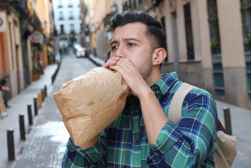 Jeune homme ethnique souffrant de ventilation exagérée dehors photographie stock