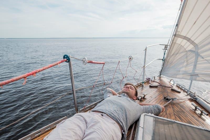Jeune homme européen se reposant sur le yacht regardant le ciel photographie stock