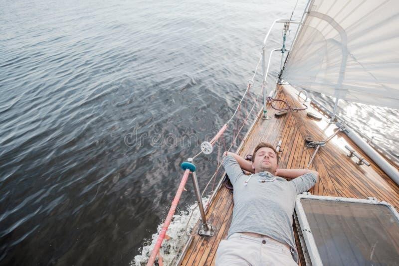 Jeune homme européen se reposant sur le yacht regardant le ciel image libre de droits