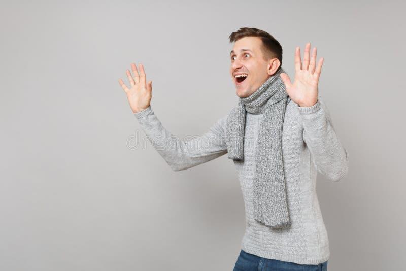 Jeune homme excité dans le chandail gris, écharpe maintenant la bouche mains grandes ouvertes et en hausse sur le fond gris Sain photographie stock