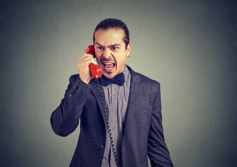Jeune homme fâché hurlant au téléphone image libre de droits