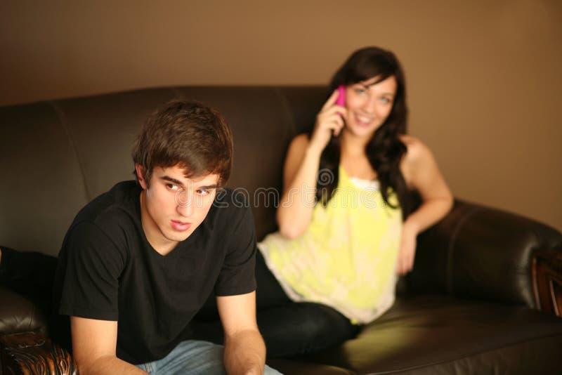 Jeune homme fâché ignoré par l'amie au téléphone image stock