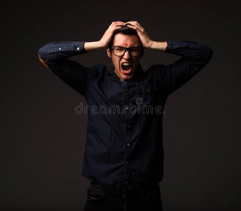 Jeune homme fâché montrant à la main image stock