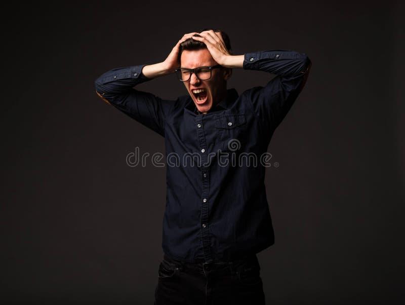 Jeune homme fâché montrant à la main photo stock