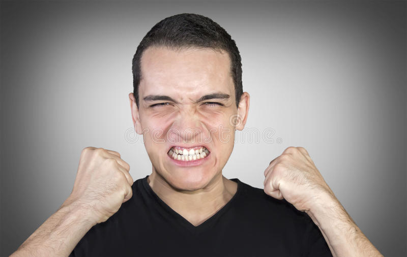 Jeune homme fâché montrant ses poings au-dessus de fond neutre photo libre de droits