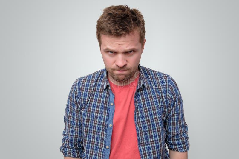 Jeune homme fâché regardant la caméra fronçant les sourcils photo stock