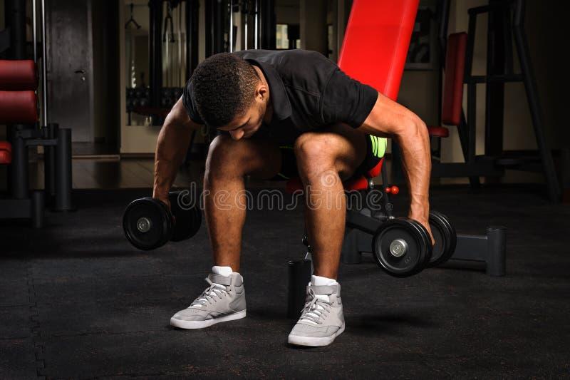 Jeune homme faisant Bent Over Dumbbell Reverse assis photographie stock libre de droits