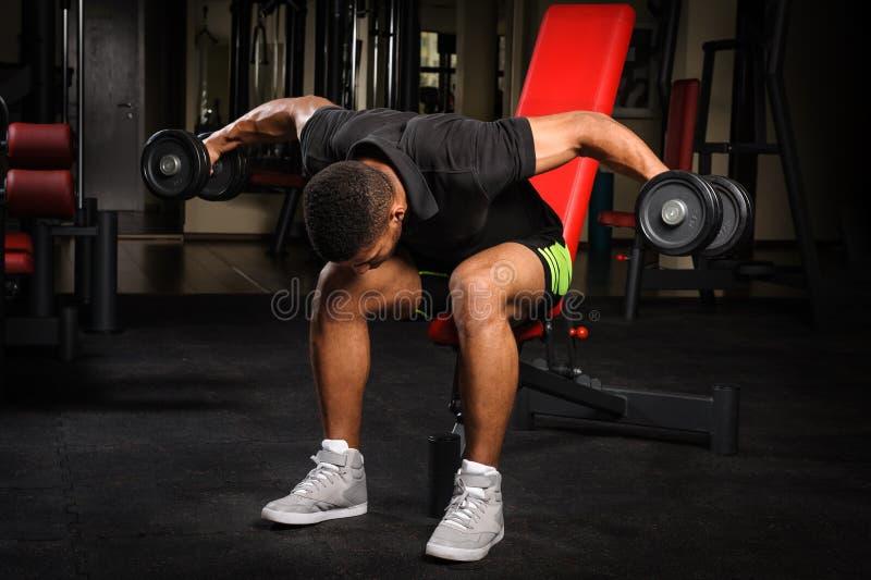 Jeune homme faisant Bent Over Dumbbell Reverse assis images libres de droits