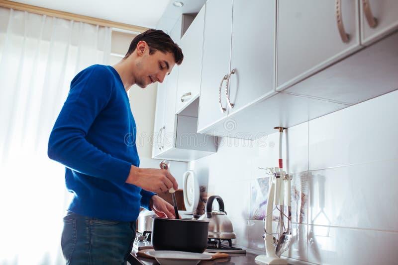 Jeune homme faisant cuire dans la cuisine à la maison photographie stock libre de droits