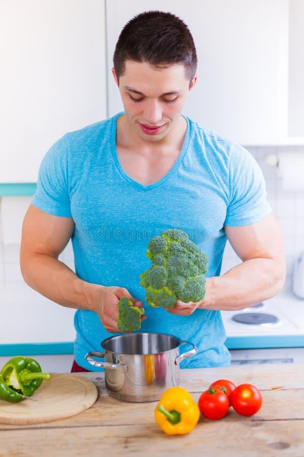 Jeune homme faisant cuire le format de portrait sain de légumes de repas dans photos stock