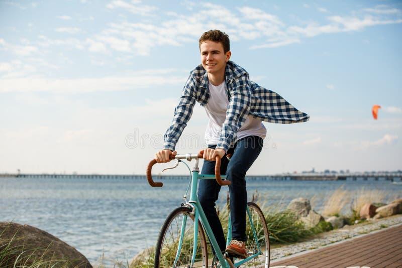 Jeune homme faisant du v?lo au bord de la mer photographie stock