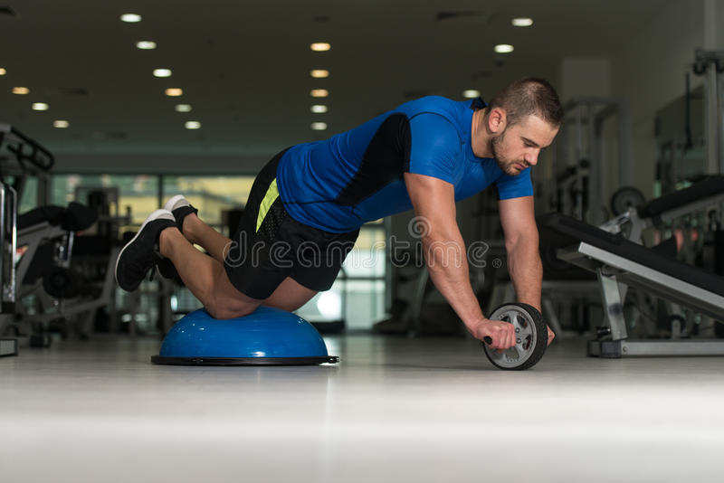 Jeune homme faisant l'exercice sur la boule d'équilibre de Bosu photo libre de droits
