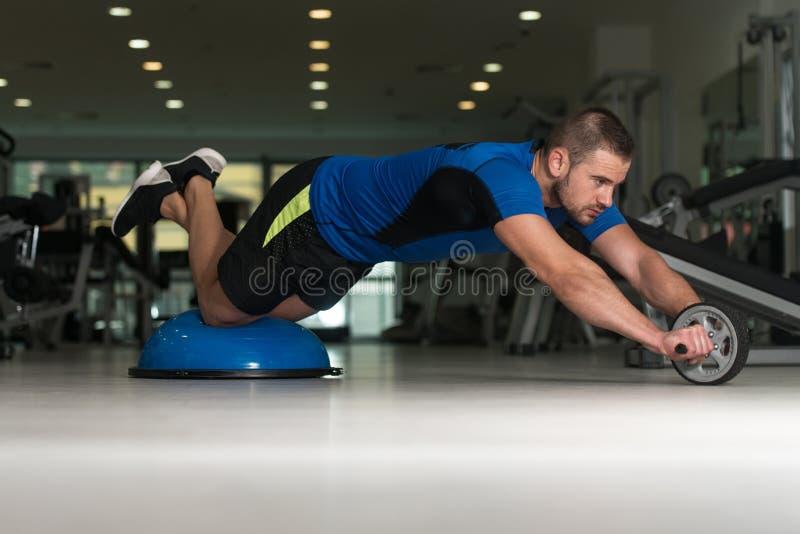 Jeune homme faisant l'exercice sur la boule d'équilibre de Bosu photographie stock libre de droits