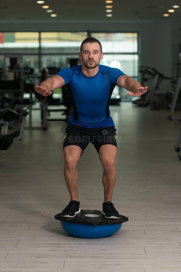 Jeune homme faisant l'exercice sur la boule d'équilibre de Bosu image libre de droits