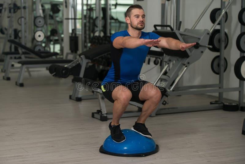 Jeune homme faisant l'exercice sur la boule d'équilibre de Bosu photo stock