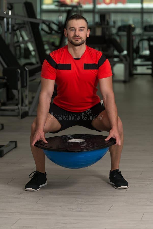 Jeune homme faisant l'exercice sur la boule d'équilibre de Bosu images libres de droits