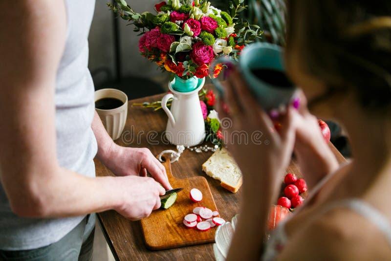 Jeune homme faisant le petit déjeuner ainsi que son amie images stock