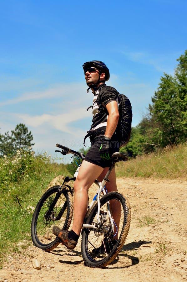 Jeune homme faisant un cycle à travers champs photo stock