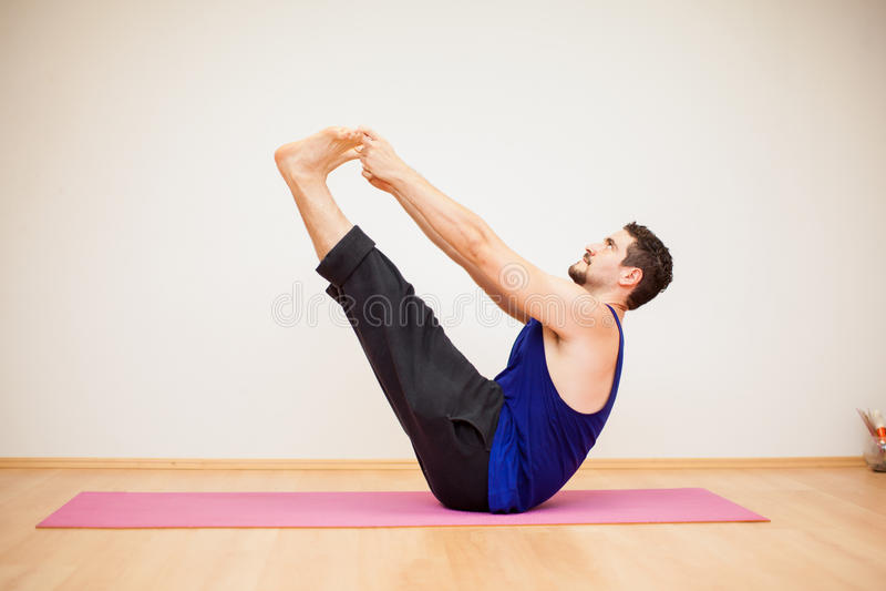 Jeune homme faisant une pose de yoga de bateau photos libres de droits