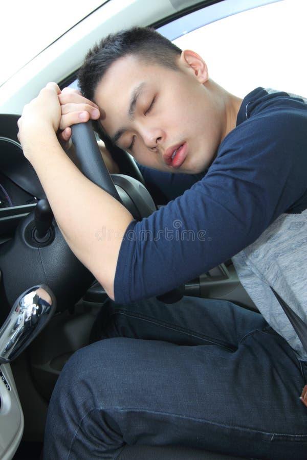 Jeune homme fatigué endormi à la roue photographie stock