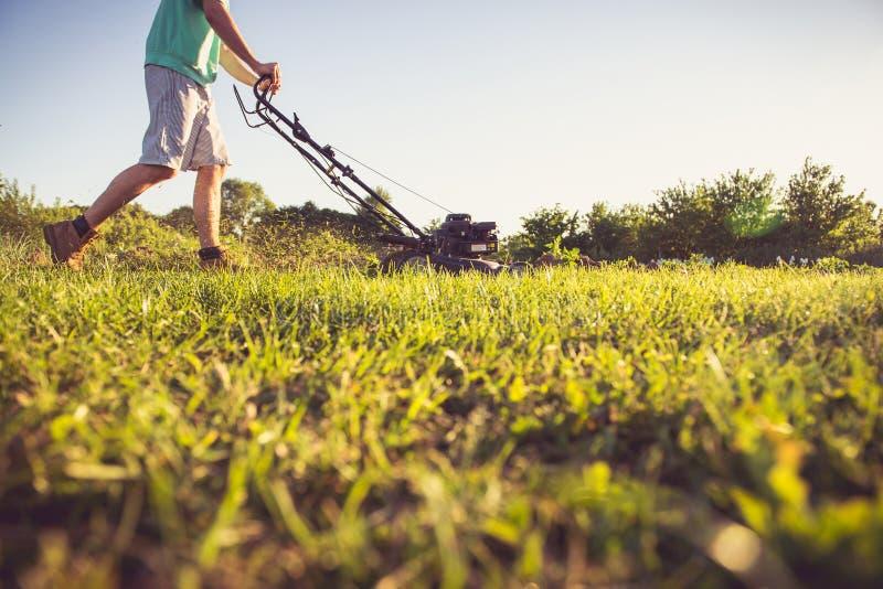 Jeune homme fauchant l'herbe photo stock