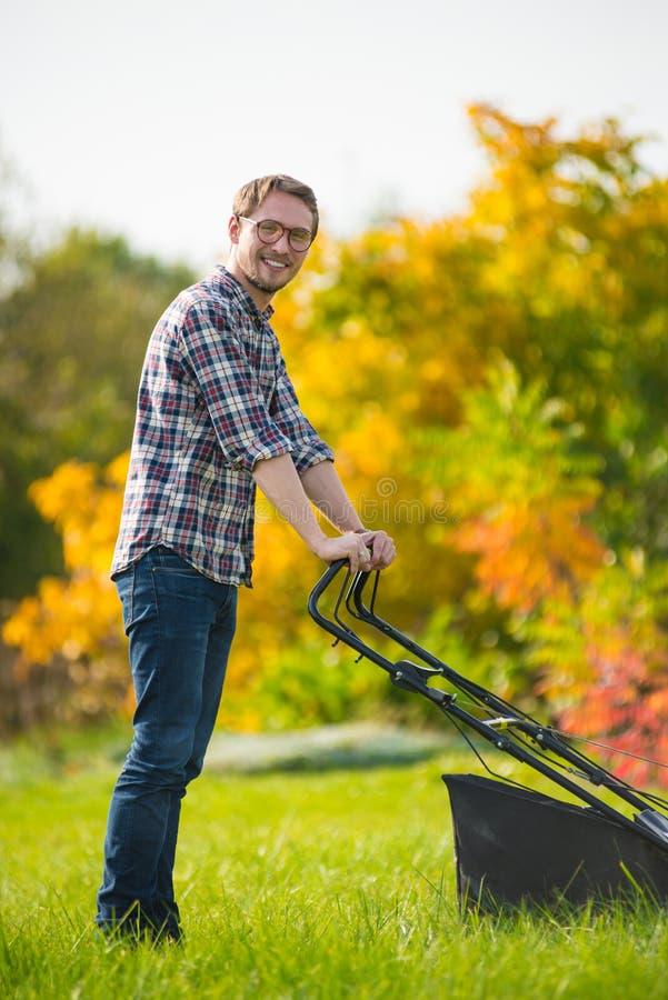 Jeune homme fauchant l'herbe photos stock