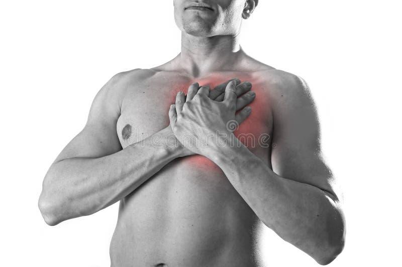 Jeune homme fort de sport de corps avec des mains sur son torse couvrant son coeur dans des problèmes coronaires de douleur thora photographie stock
