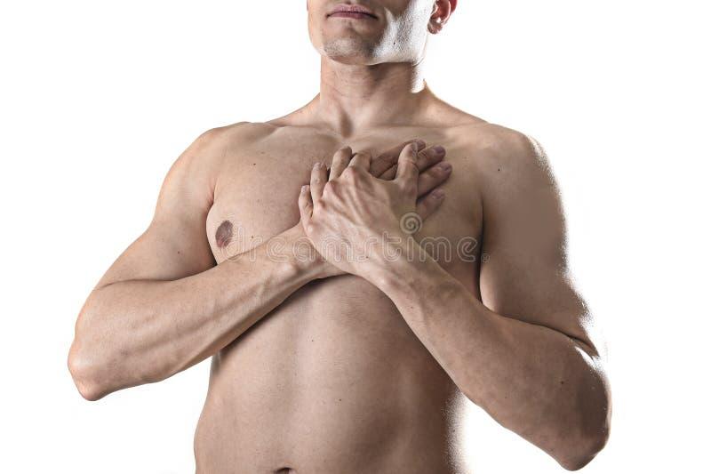 Jeune homme fort de sport de corps avec des mains sur son torse couvrant son coeur dans la douleur thoracique images stock