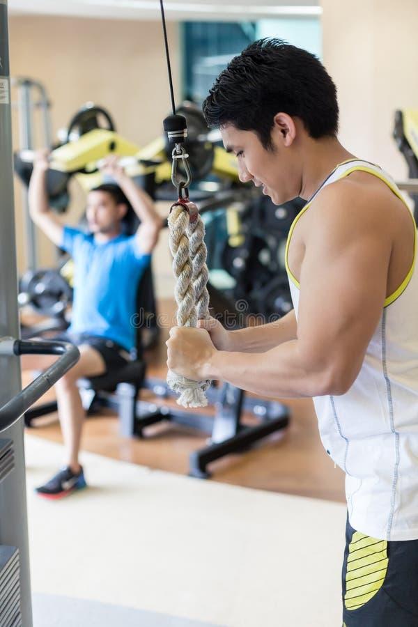 Jeune homme fort exerçant le refoulement de triceps à la machine de câble de corde image stock