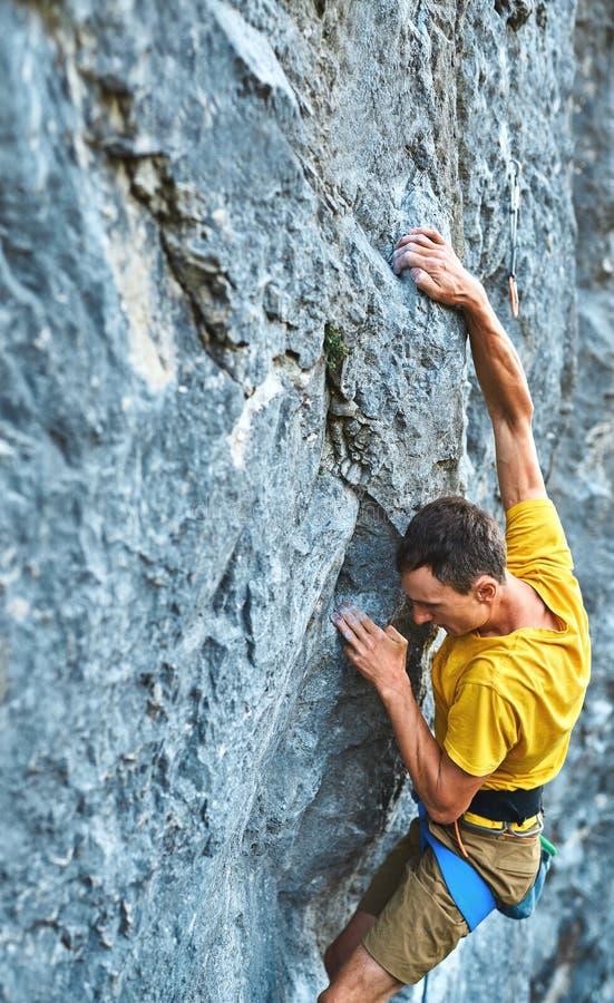 Jeune homme fort grimpant dans le rocher en t-shirt jaune, escalade sur une falaise photo libre de droits