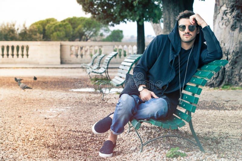 Jeune homme frais à la mode avec des lunettes de soleil détendant sur un banc photos libres de droits