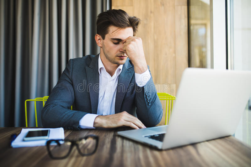Jeune homme frustrant d'affaires travaillant sur l'ordinateur portable au bureau image libre de droits